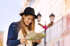 有拿着城市地图的帽子的逗人喜爱的美丽的女孩 库存图片