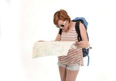 有拿着城市地图运载的背包的红色头发的年轻可爱的美国旅游妇女丢失和被混淆 免版税库存图片