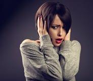 有拿着头与的短的发型的震惊不快乐的妇女 库存图片
