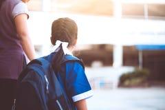 有拿着她的母亲的背包的逗人喜爱的亚裔学生女孩 免版税库存照片