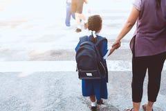 有拿着她的母亲的背包的逗人喜爱的亚裔学生女孩 图库摄影