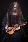 有拿着小提琴的黑面纱的白肤金发的女孩 库存图片