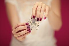 有拿着小的章鱼别针的完善的桃红色指甲油的美好的妇女手 库存照片