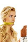 有拿着巧克力的被栓的嘴的妇女 免版税库存图片