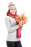 有拿着干燥叶子的冬天帽子的美丽的女孩 免版税库存图片
