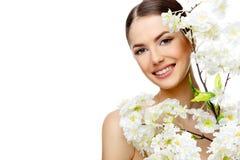 有拿着开花的分支的干净的新鲜的皮肤的美丽的妇女 图库摄影