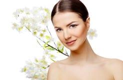 有拿着开花的分支的干净的新鲜的皮肤的美丽的妇女 免版税图库摄影
