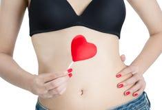 有拿着心脏棒棒糖的红色钉子的妇女手 免版税图库摄影