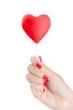 有拿着心脏棒棒糖的红色钉子的妇女手 免版税库存图片