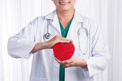 有拿着心脏的听诊器的亚裔男性医生,隔绝在白色背景 免版税库存图片