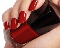有拿着指甲油瓶的理想的发光的红色修指甲的美丽的女性手指 关于女性手的关心 明亮的胶凝体 库存图片
