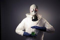 有拿着放射性液体的防毒面具的人 免版税库存图片