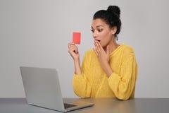 有拿着无具体金额的信用证卡片的膝上型计算机的惊奇的妇女 免版税库存照片