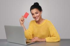 有拿着无具体金额的信用证卡片的膝上型计算机的愉快的妇女 免版税库存照片