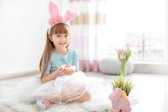 有拿着明亮的复活节彩蛋的兔宝宝耳朵的逗人喜爱的小女孩 免版税库存照片