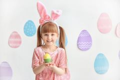 有拿着明亮的复活节彩蛋的兔宝宝耳朵的逗人喜爱的小女孩 库存照片