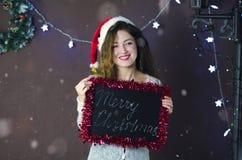 有拿着有题字的圣诞快乐的圣诞老人帽子的美丽的女孩一个黑板在圣诞节背景  免版税库存照片