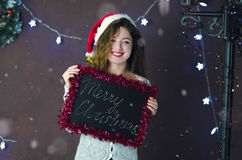 有拿着有题字的圣诞快乐的圣诞老人帽子的美丽的女孩一个黑板在圣诞节背景  库存照片