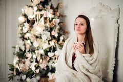 有拿着杯子热的咖啡的坐的家的年轻美丽的妇女穿被编织的温暖的毛线衣 圣诞节我的投资组合结构树向量版本 库存照片