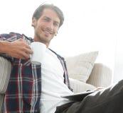 有拿着杯子的膝上型计算机的年轻人坐地板在沙发附近 免版税库存图片