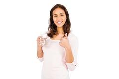 有拿着杯水的赞许的微笑的妇女 库存图片