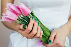 有拿着桃红色郁金香,特写镜头的绿色修指甲的女性手 免版税库存照片