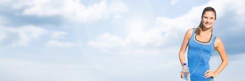 有拿着水的云彩的适合的运动妇女 库存照片