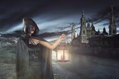 有拿着灯笼的黑斗篷的年轻亚裔巫婆 免版税图库摄影