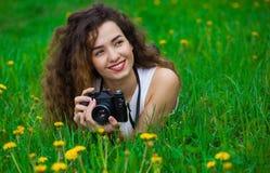 有拿着照相机和说谎在草的卷发的美丽的女孩摄影师 库存图片