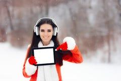 有拿着片剂个人计算机的耳机的微笑的女孩 库存照片