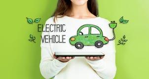 有拿着片剂的妇女的电动车 免版税图库摄影