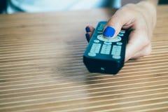 有拿着电视遥控和presse的蓝色指甲油的女性手 库存照片