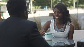 有拿着的一杯咖啡黑人女孩,谈话与她美国黑人的同事,坐在咖啡馆之外 图库摄影