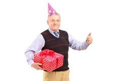 有拿着礼品和产生赞许的当事人帽子的一个绅士 库存图片