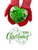 有拿着礼物的红色手套的妇女以心脏和文本圣诞快乐的形式 书法字法 库存照片