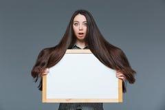 有拿着空白的委员会的长的头发的妇女 免版税库存图片