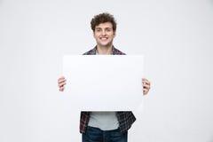 有拿着空白的广告牌的卷发的人 免版税库存图片