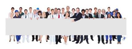 有拿着空白的横幅的各种各样的职业的人们 库存照片