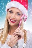 有拿着红色白的圣诞节棒棒糖的圣诞老人帽子的美丽的妇女 库存照片