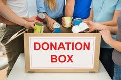 有拿着罐头的捐赠箱子的人们 库存照片