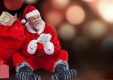 有拿着美元的礼物大袋的圣诞老人,当坐木板条时 免版税库存图片