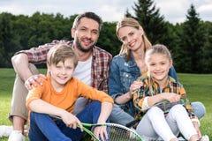 有拿着羽毛球拍和微笑对照相机的两个孩子的家庭户外 免版税库存照片