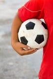 有拿着肮脏的黑白色橄榄球或socce的红色T恤杉的男孩 图库摄影