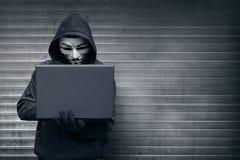 有拿着膝上型计算机的面具的戴头巾黑客,当键入时 库存图片