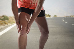 有拿着膝盖用在痛苦遭受的韧带伤害的手的强的运动腿的年轻体育妇女 库存照片