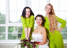 有拿着花束的女傧相的快乐的新娘 免版税库存图片