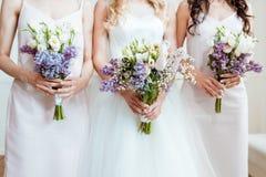 有拿着花束的女傧相的新娘 免版税库存照片