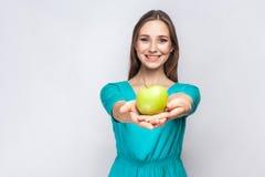 有拿着苹果和分享与微笑的雀斑和绿色礼服的年轻美丽的妇女 演播室射击, 免版税库存照片