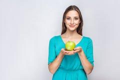 有拿着苹果和分享与微笑的雀斑和绿色礼服的年轻美丽的妇女 库存图片