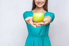 有拿着苹果和分享与微笑的雀斑和绿色礼服的年轻美丽的妇女 免版税库存图片